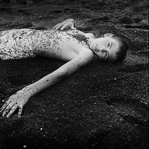 boy laying in black sand