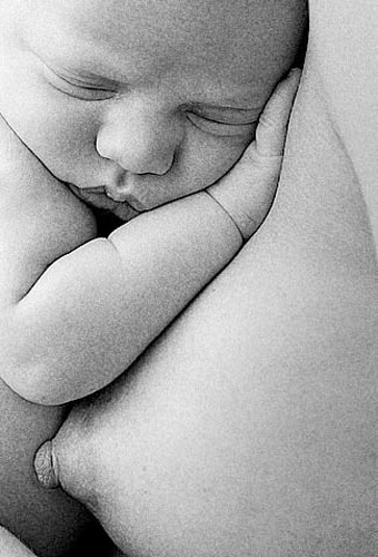 black and white artistic newborn photo of mom and baby nursing nude